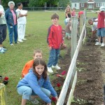 Master Gardeners planting garden with local children.